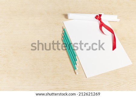 Scroll of paper with a red ribbon and pencils on a wooden surface. - stock photo