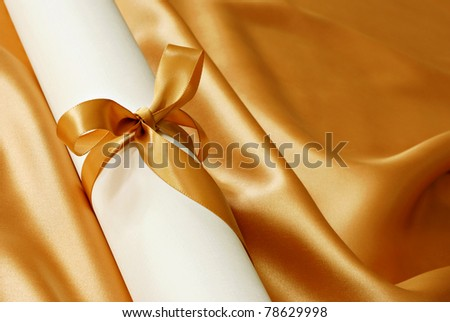 Scrolled paper (diploma, certificate or announcement) tied with gold satin ribbon on elegant gold fabric background.  Macro with shallow dof and copy space. - stock photo