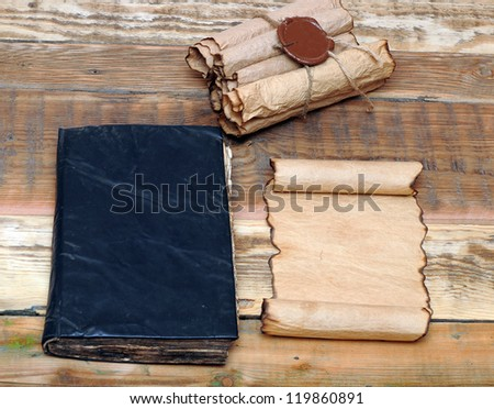 Scrolls of vintage paper with old book - stock photo