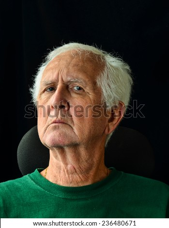 Scruffy Gray haired senior man with questioning expression on face.  Vertical Head and shoulders  against black background with copy space. - stock photo