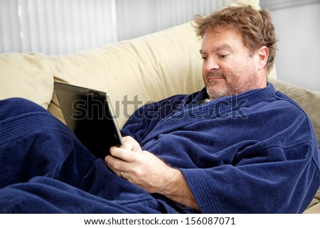 Scruffy looking unemployed man sitting home in his bathrobe using his tablet PC.   - stock photo