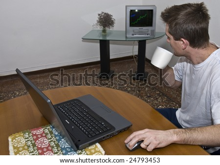 Scruffy man in front of laptop watching stock graphic on TV.