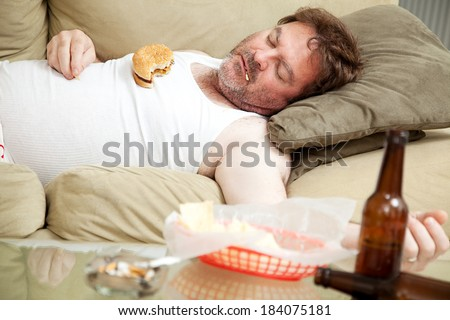 Scruffy unemployed man passed out on the couch in his underwear, surrounded by cigarettes, junk food, and beer bottles.