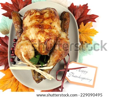 Scrumptious roast turkey chicken on platter with festive decorations for Thanksgiving lunch with autumn Fall leaves on white table, with copy space. - stock photo