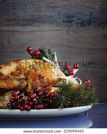 Scrumptious roast turkey chicken on platter with festive decorations for Thanksgiving or Christmas lunch, against dark recycled wood background. Vertical with copy space. - stock photo