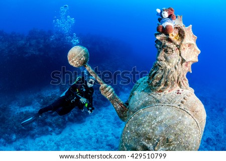 SCUBA diver and a large underwater statue - stock photo