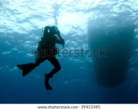 Scuba Diver Clearing Mask while Descending under the Boat - stock photo