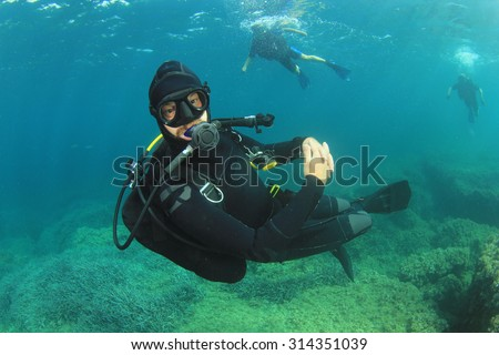 Scuba diver diving instructor underwater - stock photo