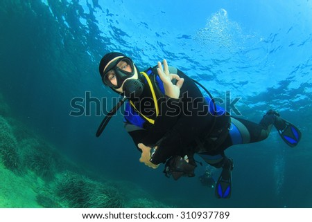 Scuba Diver diving underwater - stock photo
