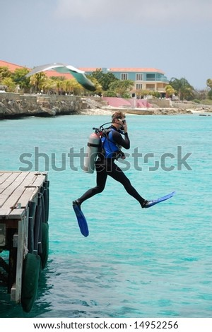 "Scuba diver doing perfect ""giant stride"" off dock. - stock photo"