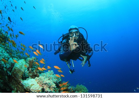 Scuba Diver explores coral reef with tropical fish - stock photo