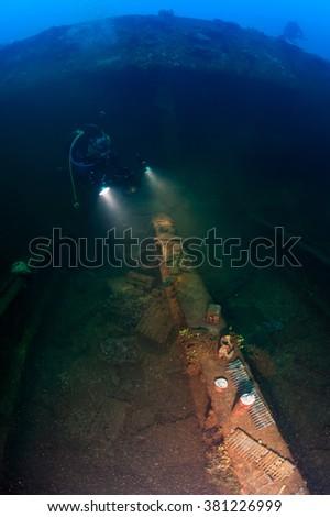 Scuba diver exploring amonition inside cargohold of wreck ship in the deep.  - stock photo