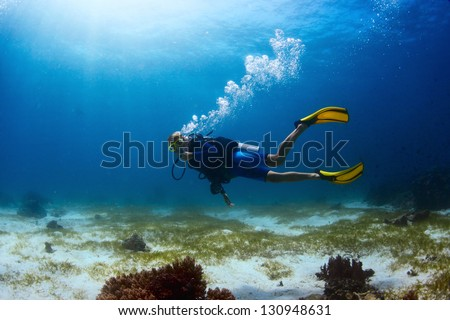 Scuba diver exploring tropical dive site and finning over bottom - stock photo