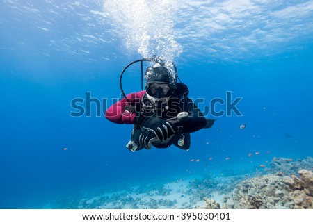 Scuba diver floating over coral reef in the Red Sea and looking to the camera. - stock photo