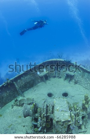 scuba diver fly's over a underwater ship wreck - stock photo