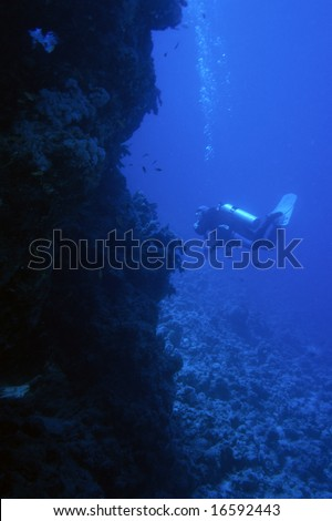 Scuba diver in deep blue underwater world landscape. Only blue light at this depth.Red sea Egypt. Scanned from film.