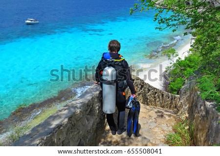 Scuba diver on the way to the water. Stairs to the ocean beach with diver girl. Tropical paradise beach with azure sea, ship and scuba diver.