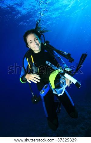 Scuba Diver removes her mask - stock photo
