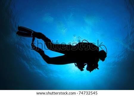 Scuba Diver silhouette against sunburst - stock photo
