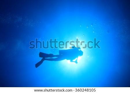 Scuba diver silhouette sun - stock photo