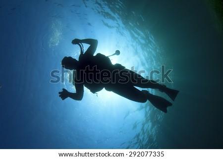 Scuba diver silhouette underwater - stock photo