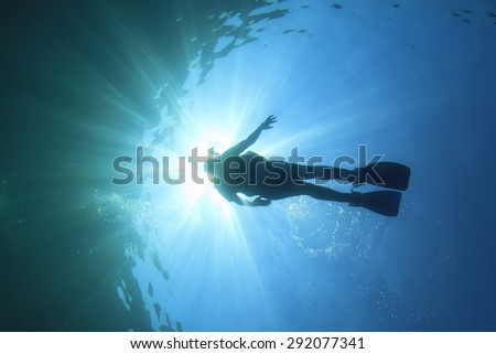 Scuba diver silhouette underwater - stock photo