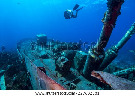 Scuba diver swimming over the stern of the Willaurie wreck - stock photo