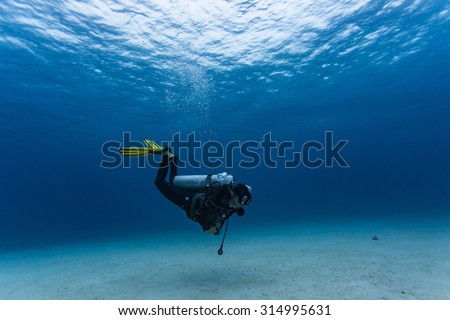 Scuba diver swims over a sandy bottom shallow. - stock photo
