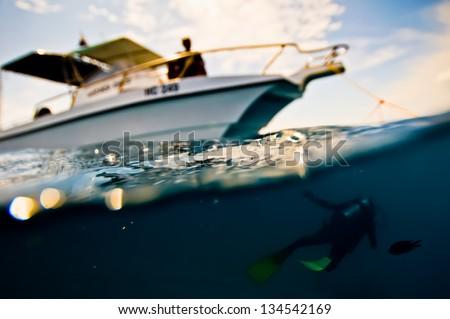 Scuba diver swims under a boat - stock photo