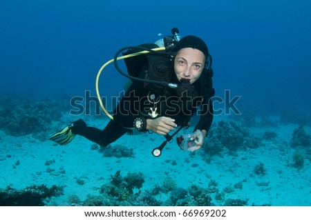 scuba diver takes her mask off underwater - stock photo