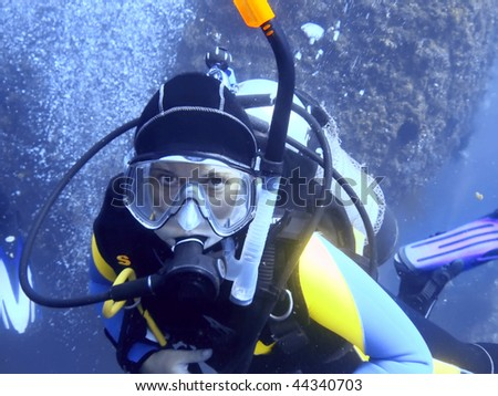 Scuba diver underwater looking at camera. - stock photo