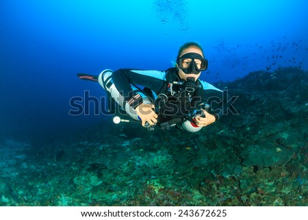 SCUBA diver using twin sidemount tanks deep underwater - stock photo
