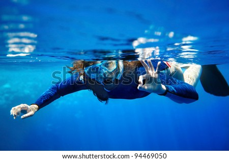 Scuba diver young woman in  blue water. - stock photo