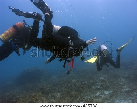 Scuba divers at 15 metres depth off Perhentian Island, Malaysia - stock photo