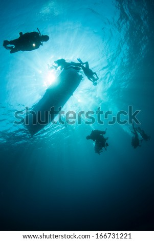 Scuba divers descend from their boat into the unknown. The divers are exploring a coral reef in Indonesia where marine diversity is very high.