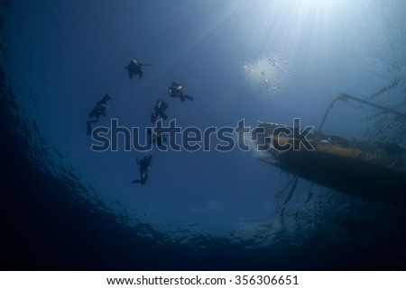 Scuba divers descending down into the abyss