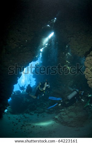 Scuba divers exploring the inside of an underwater cave. Jackfish alley, Ras Mohamed National Park, Red Sea, Egypt. - stock photo