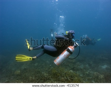 Scuba divers in Malaysian waters off Perhentian Island - stock photo
