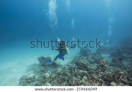 Scuba Divers passing through tropical coral reef. - stock photo