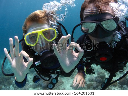 Scuba divers showing OK signal underwater - stock photo