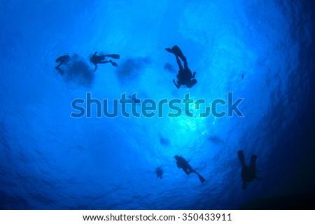 Scuba divers silhouette against sea surface - stock photo
