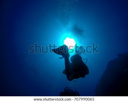 Scuba Divers Silhouette Against Sun. Group of scuba divers ascending. A backlit scuba diver silhouette. View of the scuba diver and air bubbles in the deep blue sea against the sunlight.