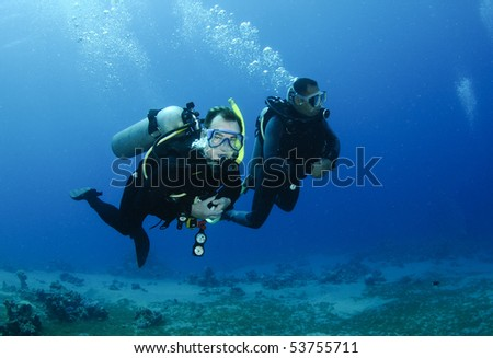 scuba divers swim in clear blue water - stock photo
