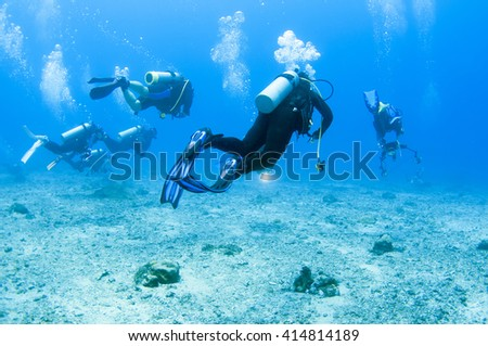 Scuba divers swim over colorful tropical coral reef - stock photo