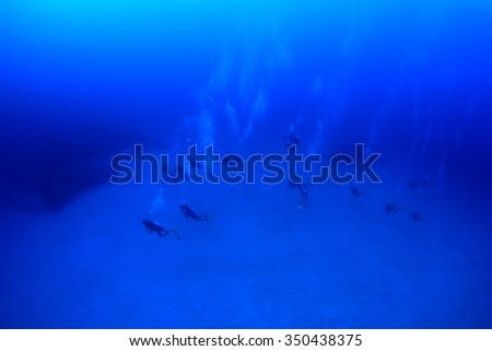 Scuba divers swimming in ocean - stock photo