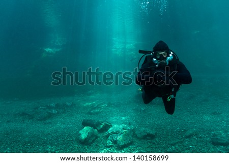 Scuba Diving Alps lake. Cold blue crystal clear water with sun-rays.Austria. - stock photo