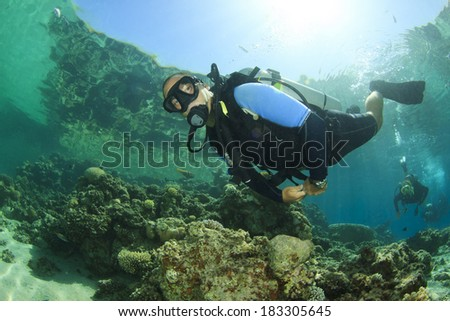 Scuba diving in clear blue water on coral reef - stock photo