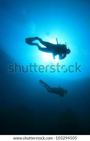Scuba Diving in the Ocean: Silhouettes against sunburst - stock photo