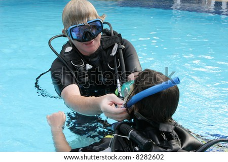 Scuba diving instructor demonstrates a skill to a student in a swimming pool.