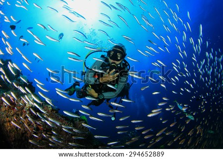 Scuba diving with fish on coral reef - stock photo